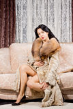 Glamorous beautiful woman. Sitting looking at the camera while posing on a couch in bare legs and a fur coat royalty free stock images