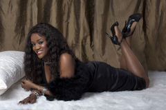 Glamorous black woman. A young glamorous black woman laid on a bed wearing a black dress and high heeled shoes Royalty Free Stock Image