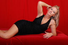 Glamorous blond. Beautiful blond woman wearing a black dress laying on her side with one hand above her head, red background Stock Photography