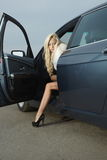Glamorous blond babe near tuned super car Royalty Free Stock Images