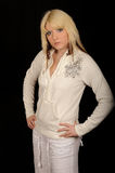 Glamorous Blond Woman. A glamorous blond woman posing in a white dress, on black studio background Royalty Free Stock Photography