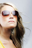 Glamorous blond woman in sunglasses. With her hair blowing in the breeze staring off thoughtfully into the distance with a serious expression Royalty Free Stock Photography