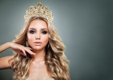 Glamorous Blonde Woman with Golden Crown. Makeup and Wavy Hair. Cute Fashion Model with Diamonds Jewelry, Shiny Curly Hairstyle and Make up Royalty Free Stock Image