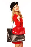 Glamorous Blonde Woman Out Shopping. Glamorous blonde woman in a fashionable red ensemble out shopping with a large decorative carrier bag Stock Photography