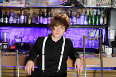 Glamorous boy in black shirt and white suspenders sits Royalty Free Stock Photography