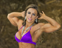 Glamorous Brazilian Biceps. Gorgeous Brazilian fitness and figure model and Ms. Olympia Physique champion, Juliana Malacarne, flexes her defined biceps while Royalty Free Stock Image