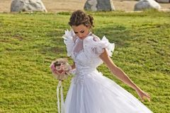 Glamorous Bride. A young glamorous bride in a white dress with puffy sleeves stands in the meadow of a park looks down stock image