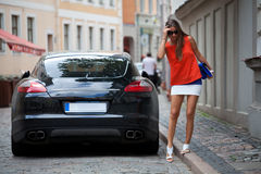 Glamorous brunet near luxury car Stock Photos