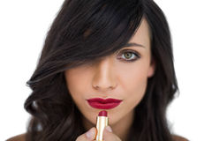 Glamorous brunette applying red lipstick Royalty Free Stock Photo