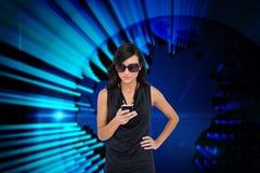 Glamorous brunette using smartphone against blue technology background Stock Photography