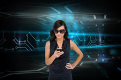 Glamorous brunette using smartphone against circuit board Stock Photo