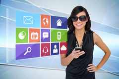 Glamorous brunette using smartphone with app icon menu Royalty Free Stock Photography