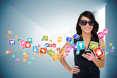 Glamorous brunette using smartphone with app icons Royalty Free Stock Image