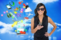 Glamorous brunette using smartphone with app icons and laptop Stock Images