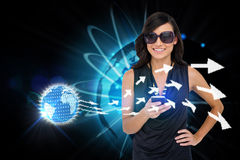 Glamorous brunette using smartphone with earth and arrows Stock Photography