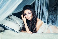 Glamorous Brunette Woman in White Bedroom Royalty Free Stock Photo