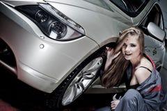 Glamorous Car Mechanic. A beautiful brunette model posing in a car mechanic uniform, repairing a car in a garage stock photography