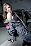 Glamorous Car Mechanic. A glamorous brunette model wearing a mechanic uniform in a provocative pose in front of a car in a garage stock photos