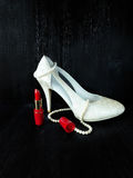 Glamorous composition made of white heels, red lipstick and pearl necklace Royalty Free Stock Photo