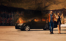 Glamorous couple leaves from burning car Stock Images