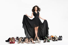 Glamorous curvy brunette woman. Inside the Studio woman in black dress with gorgeous long dark hair among the shoes Royalty Free Stock Photos