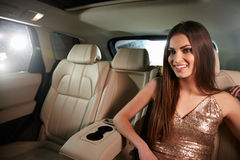 Glamorous dark haired young woman sitting in back of a limo Royalty Free Stock Photo