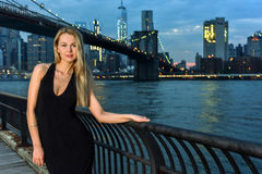 Glamorous and elegant young woman in black evening dress posing outdoor in front of Brooklyn Bridge. Royalty Free Stock Photos