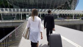 Glamorous female and bodyguard with her luggage walking at airport, tourism stock photos