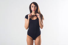 Glamorous female standing in studio, posing for portrait, wearing large sunglasses and one piece black bodysuit, holding Royalty Free Stock Photography