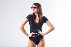 Glamorous female standing in studio, posing for portrait, wearing large sunglasses and one piece black bodysuit, holding Royalty Free Stock Image
