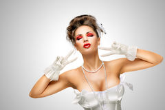 Glamorous gesture. Sexy pinup bride in a vintage wedding corset showing V sign on grey background Stock Images