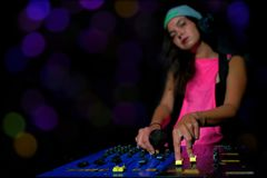 Glamorous girl deejay at work mixing sound on her console at a p. Arty or night club with colorful strobe lights background Stock Photo