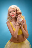 Glamorous girl holding a chihuahua dog. Blonde hugging a puppy. Yellow dress on a blue background Royalty Free Stock Image