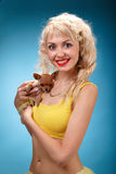 Glamorous girl holding a chihuahua dog. Blonde hugging a puppy. Yellow dress on a blue background Stock Photo