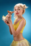 Glamorous girl holding a chihuahua dog. Blonde hugging a puppy. Yellow dress on a blue background Stock Photography