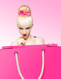 Glamorous girl with huge shopping bag on pink Stock Photos