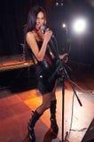 Glamorous girl singing on the stage stock photo