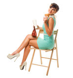 Glamorous girl in turquoise dress holds snacks sit on chair Stock Images