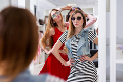 Glamorous girls trying on sunglasses posing in front of the mirror in fashion boutique.  Stock Photo