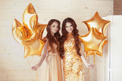 Glamorous ladies party, two women in fashion golden dresses with. Bright stars balloons.  Celebration. Happy birthday background Stock Photo