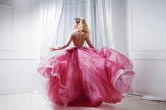 Glamorous lady in a chic pink dress with a train. Studio portrait in white interior, back view Stock Images
