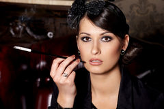 Glamorous lady with cigarette. Glamorous brunette woman holding cigarette in mouthpiece in bar Stock Photography