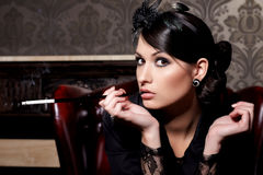 Glamorous lady with cigarette. Glamorous brunette woman holding cigarette in mouthpiece in bar Stock Images