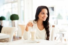 Glamorous lady drinking coffee. In a beautiful cafe Royalty Free Stock Photography