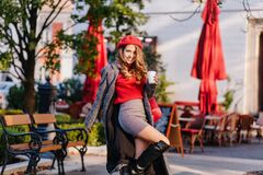 Glamorous lady in elegant knee high boots dancing in park with cup of coffee. Outdoor portrait of womantic woman in red