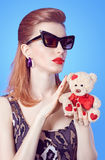 Glamorous lady girl in glasses, Loving teddy bear with hearts. Glamorous fashion lady girl with red lips in glasses and dress with leopard print holds in hands Royalty Free Stock Photos