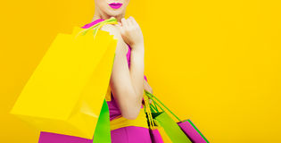 Glamorous lady with shopping. On bright yellow background Stock Image