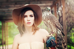 Glamorous Lady in Vintage Hat with Bird. Glamorous Lady in Vintage Hat with Hunter Bird stock image