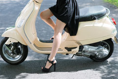 Glamorous legs. Glamorous girl wearing stylish gown and footwear sitting on scooter Royalty Free Stock Images