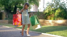 Glamorous little girl in shoes high heeled with many shopping bags in hands walking after visiting expensive boutiques. Glamorous little girl in shoes high stock footage
